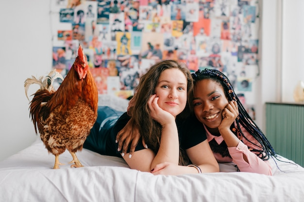 Счастливые веселые молодые женщины, лежа на кровати с курицей