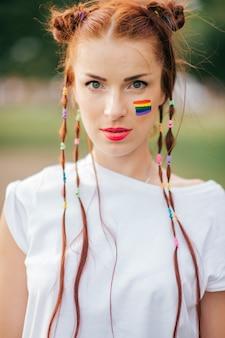 Рыжие волосы женщина с флагом лгбт на лице
