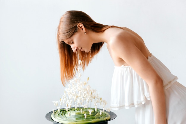 屋内花春花束組成物の臭いがする白いギリシャスタイルのドレスでかなり若い女性。