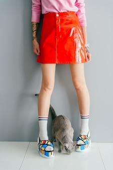 カラフルなファッショナブルなハイウェッジレザーサンダルで女性の足の間に横たわる猫