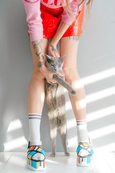足の間ロシア青猫を保持している流行の服の女性のファッションの肖像画