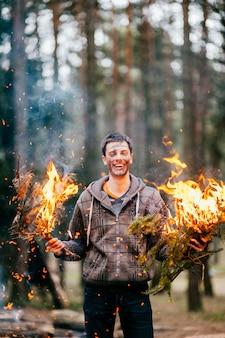 Счастливый сумасшедший человек держит в руках горящие дрова