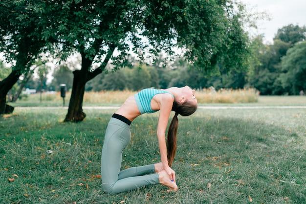 Брюнетка фитнес девушка делает йогу на открытом воздухе.