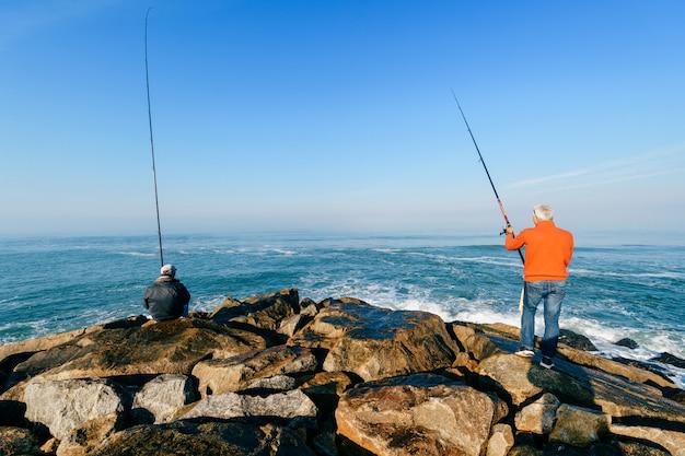 ポルトガルの大西洋の朝。認識できない成人男性の釣りのグループ。釣り竿を持つ未知の漁師。