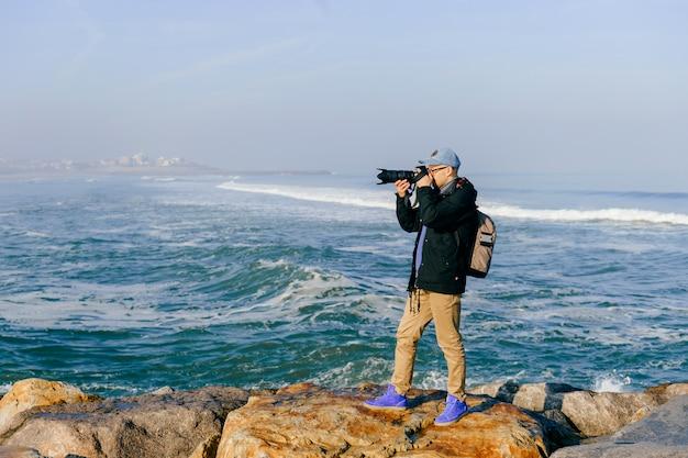 Взрослый путешественник человек принимает фото красивый пейзаж от мыса океана в португалии с профессионалом в солнечное утро.
