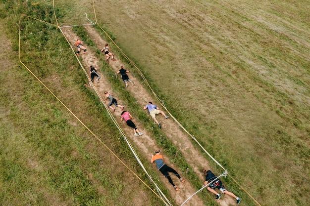 Молодые люди ползут под колючей проволокой вид сверху.