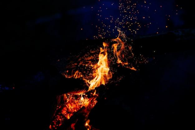 夜に燃える木。山の自然で観光キャンプでキャンプファイヤー。暗い夜には炎と火が火花を散らします。屋外でバーベキューを調理します。
