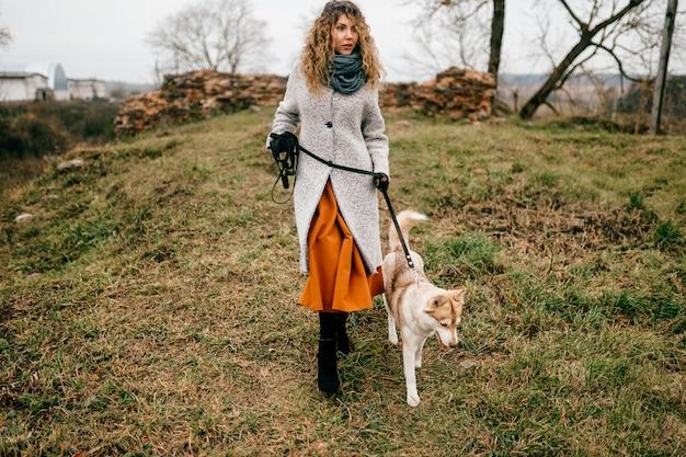 巻き毛と田舎で屋外彼女のハスキーの子犬と歩いて情熱的な感情的な顔を持つ魅力的な若い女の子。