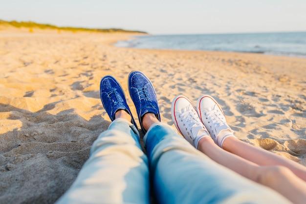 海の近くのビーチで横になっている男性と女性の足。