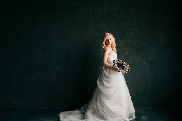 Чувственная белокурая модель в свадебном платье позирует