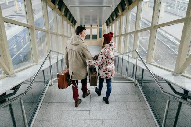Молодые счастливые любовники несут винтажные коричневые чемоданы на железнодорожной станции