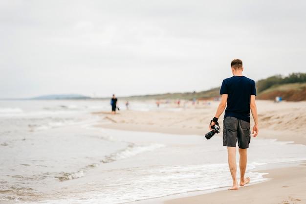 夏のビーチに沿って歩く彼の手でカメラを持つ孤独な写真家