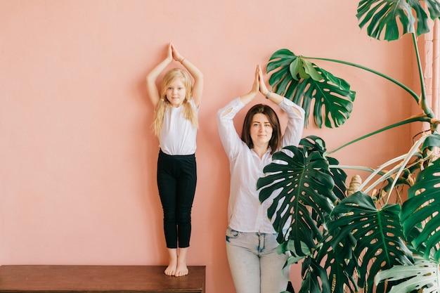 Мать и ее дочь стоя в йоге представляют над розовой стеной в студии.