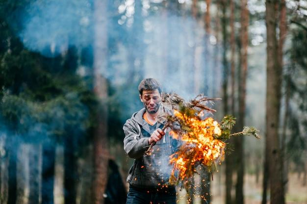 Счастливый человек с грязным лицом и эмоциональным выражением держит горящие ветви в руках в лесу.