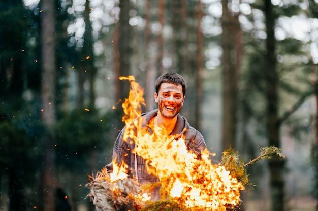 Счастливый сумасшедший веселый человек, держащий в руках горящие дрова