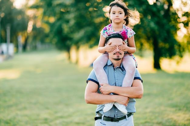 面白い表情の顔を作る肩に娘を持つお父さんの珍しいカップルのライフスタイル日没の肖像画。夏の自然を屋外で遊んで幸せな家族。父権と子供時代。お父さんは彼の女の子が大好き