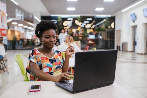 Красивая молодая темнокожая женщина фрилансера используя портативный компьютер сидя на таблице кафа. концепция внештатной работы.