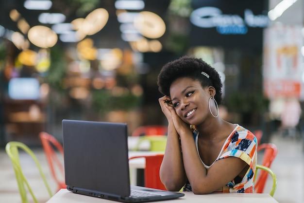 ノートパソコンとカフェのテーブルに座っていると画面を見て若いアフリカ系アメリカ人の女の子。ダークスキンのフリーランサーのコンセプト。