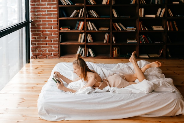 Молодая девушка в неглиже читает книгу в постели
