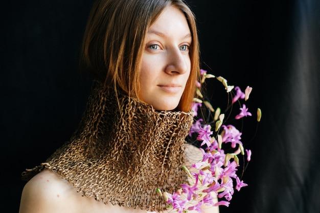 白と黒の壁に分離された青い目をした美しい少女の創造的な気分の肖像画。珍しいアートデザインの花の組成。ファッションスタイル。オリジナルの手作りの装飾が施されたきれいな女性