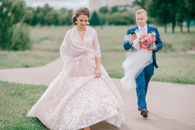 屋外の花嫁のベールを運ぶ新郎。