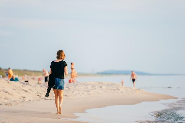 夏のビーチに沿って歩く女性。