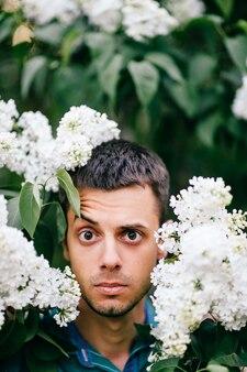 咲くライラックの茂みを通して表現力豊かな男性の肖像画