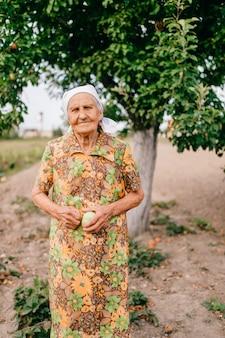 リンゴの木の前の庭に立っている手で青リンゴと孤独な老婆。