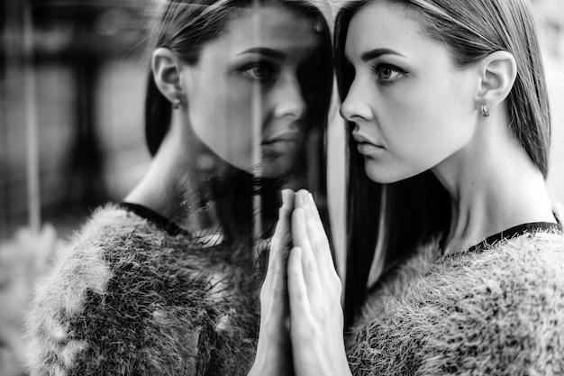 ミラー化されたウィンドウで若い女性の自己反射の肖像画。
