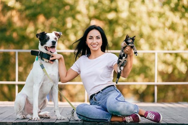 Портрет образа жизни красивой женщины брюнет с сидеть маленькой кошки и большой собаки внешний в парке.