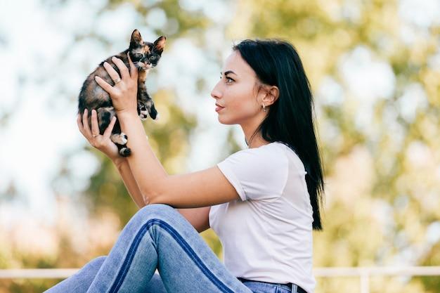 Молодая женщина сидит боком и смотрит на котенка в ее руках