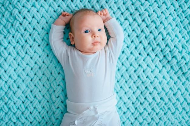 Прекрасный новорожденный ребенок с голубыми глазами, лежа на кровати.
