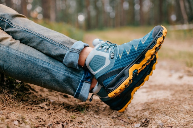 Мужские ножки в походных ботинках для активного отдыха на лесной дороге
