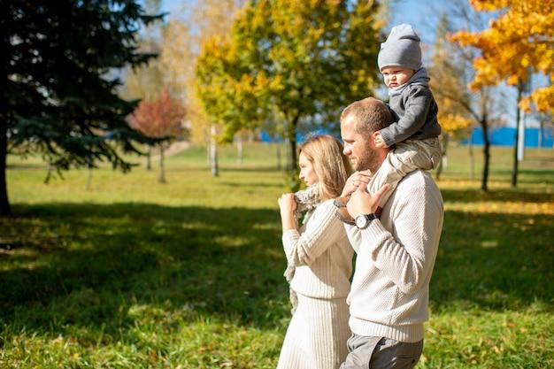 Счастливая семья гуляя с их ребенком на плечах в солнечном парке.