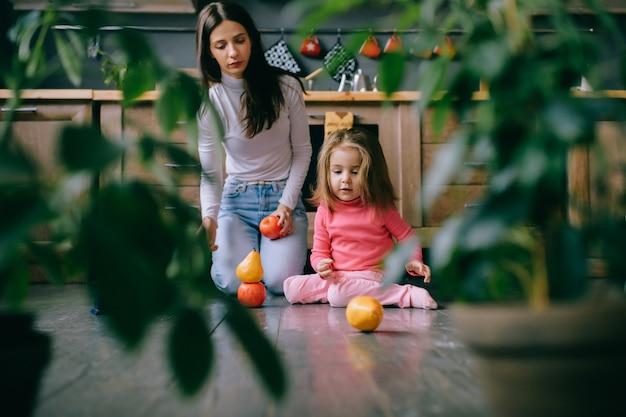 Молодая мама играет со своей маленькой дочерью, используя фрукты.