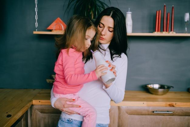 Прелестная женщина играя с ее маленькой дочерью в кухне.