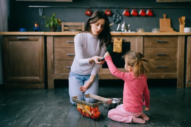 Молодая женщина, играя со своей маленькой дочерью на кухне.
