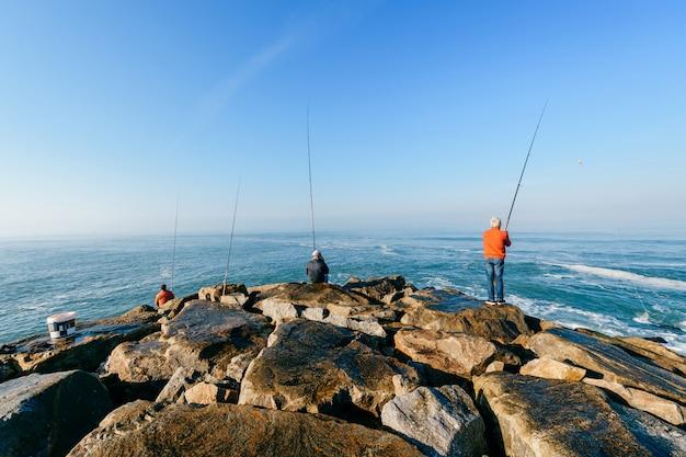 海で釣りをする男性のグループ