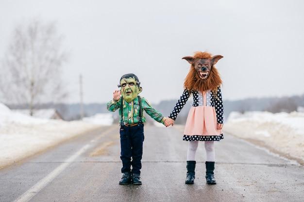 不気味なホラーシリコンマスクの肖像画で面白いハロウィーンの子供たち。冬のハロウィーンを祝う恐ろしいメイクと小さなコミカルな子供たち。田舎の休日。フランケンステニンと狼男のマスク