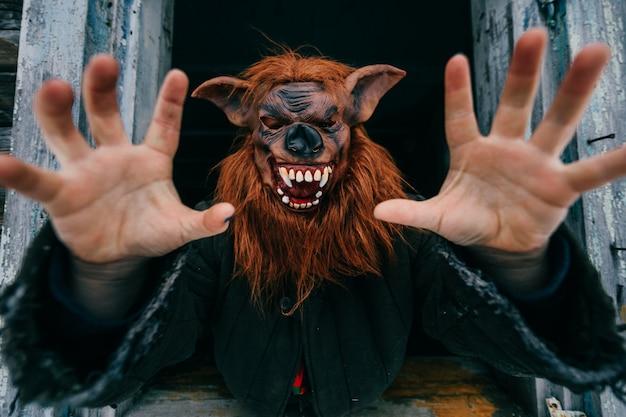 古い木製の幽霊の家の窓から外を見て不気味な恐ろしい狼男マスクを持つ未知の人。ハロウィーンのコンセプト。不気味な恐ろしい恐ろしいモンスター。子供たちは恐れます。恐ろしい物語。悪夢