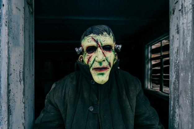 古い木製の幽霊の家の窓から外を見て不気味な恐ろしいラテックスマスクを持つ未知の人。ハロウィーンのコンセプト。不気味な恐ろしい恐ろしいモンスター。子供たちは恐れます。恐ろしい物語。悪夢。