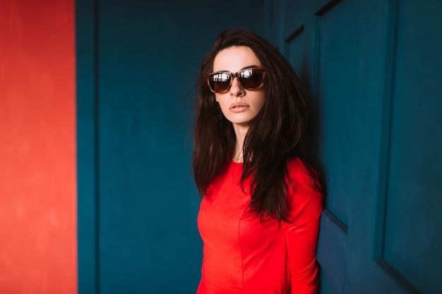赤い壁でポーズをとって赤いドレスに黒い長い髪のファッション女性