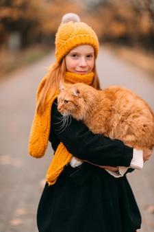 秋の公園で彼女の猫を保持しているそばかすのある顔を持つ少女。