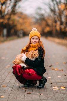 秋の公園の谷でポーズをとる彼女の膝の上の子猫と美しいそばかすの子。