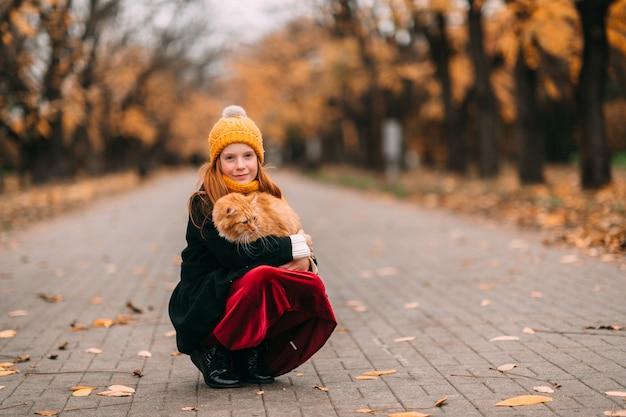 の公園の谷でポーズをとって彼女の膝の上の素敵な子猫と若いそばかす少女。