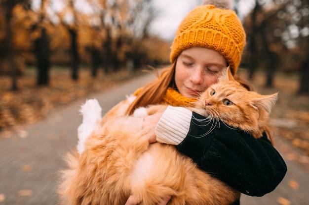 秋の公園の谷で赤い猫を保持している愛らしいそばかす少女。
