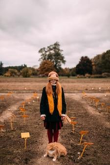 Длинноволосая девушка с завязанными глазами, стоя в осенние поля с кошкой, сидя возле ее ног.