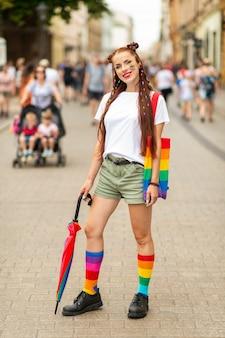 Образ жизни портрет красочной девушки с флагом лгбт на лице, позирует на улице