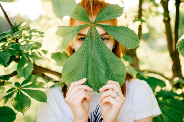 Молодая девушка прячется за листья дерева