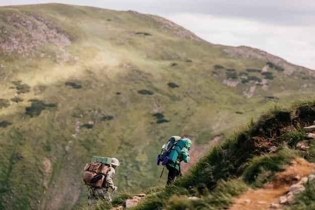 Путешественники с рюкзаками и профессиональным туристическим снаряжением поднимаются по карпатским горам. тяжелые походы. покорение высоких холмов. тяжелый багаж. достигая вершины. альпийская ходьба. каникулы. образ жизни